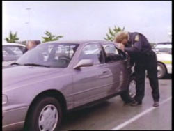 A police officer peering into a grey sedan abandoned in a parking lot.