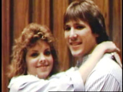 A man and woman, both with brown mullets and white shirts, hugging.