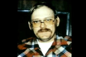 A middle aged man with a mustache and orange tinted glasses, Lee 'Dub' Wackerhagen, wearing a plaid shirt.