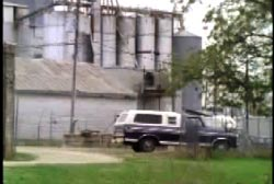 A blue and white pick up truck parked infront of farm silos.