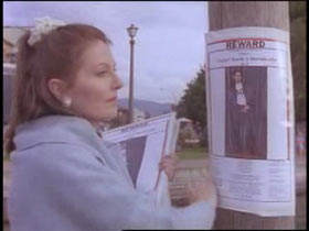 Denise Allen putting up missing posters with a reward on a street pole.