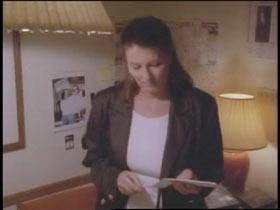 Denise Allen standing in her living room holding a envelope.