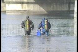 Two men in scuba gear wade into the water under a bridge