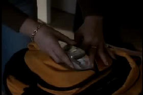 A cell phone is found in a light brown leather purse.