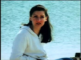 Claudia Kirschhoch wearing a oversized white sweater, she is sitting on a beach with the water behind her.