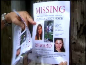 A missing poster for Claudia is stapled to the pole of a street light.