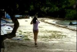 A woman walking down a beach in a white shirt and shorts.
