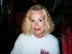 A middle aged caucasian woman with should length blech blonde hair and wearing a white sweater, Colleen Wood.