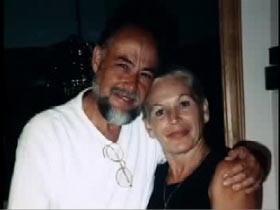 Colleen Wood posing next to her significant other, John Paul. He is a middle aged caucasian man with a black and grey beard.