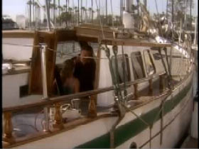 A sailboat with green trim and John Paul is hunched over in the interior cabin.