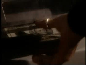 A hand with a gold ring on the thumb is reaching for a stack of money.
