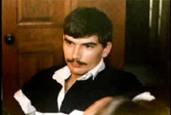 A caucasian man with short brown hair and a mustache wearing a black and white striped shirt, Curtis Pishon.