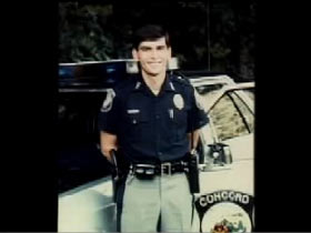 Curtis Pishon posing in his police uniform infront of his patrol car.