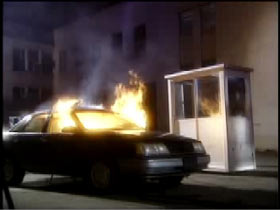 A sedan is on fire in front of security booth on a parking lot.
