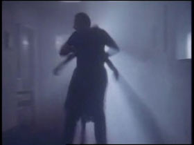 A man is dragging a woman down a hallway, both of them are in shadows.