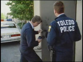Two Toledo police officers are trying to pull fingerprints off a door.