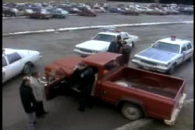 A red pick up truck surrounded by police officers and three patrol cars.
