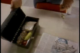 An open lunch box, a ring of keys and a newspaper are laid out on a table.