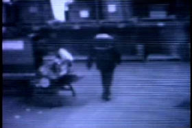 An image for a security camera, a man in a mask walking through a lobby.