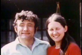 Dottie Caylor posing with her husband, Jule Caylor. He has short curly dark hair and a collared shirt.