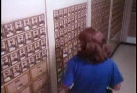 A woman in a blue shirt walking past rows of PO boxes.