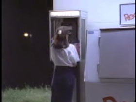 A woman in a white sweater and jeans standing at a payphone.
