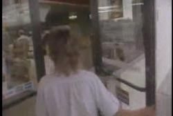 A woman in a white shirt entering a convenience store.