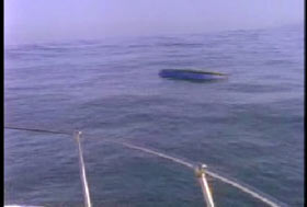 An overturned boat is bobbing in the water.