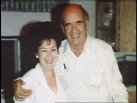 Jean Moore posing with Al Henderson, an elderly caucasian man with a bald head.