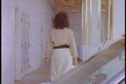 A woman in a white outfit walking from a car into the entrance of a casino.