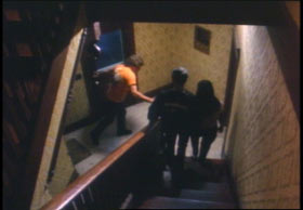 Two people walking down the stairs towards the entrance of a building as a man in orange shirt enters.