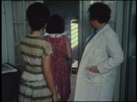 Two women walk past a doctor in a lab coat into an examine room.