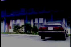 A dark sedan parked in front of a motel.