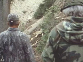 Two men in camo walking down a trail in the woods.