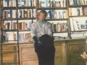 A man dancing with a black dog in front of a large bookshelf.