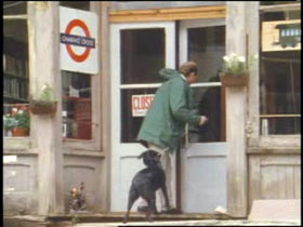 A man walking into a small shop with a black dog.