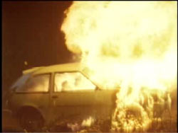A two door compact car on fire.