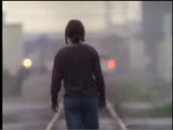 A person with short hair walking down train tracks.