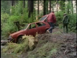 A red sedan is found by two people after being abandoned in a forest.
