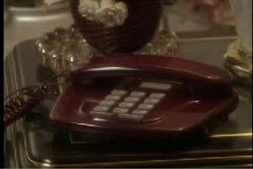 A red landline phone on a mirror top table.
