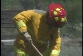 A firefighter bending down to shift through the debris.