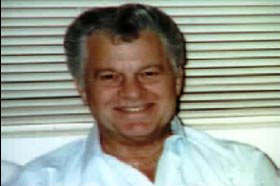 An middle aged caucasian man, Lee Young, wearing a white collared shirt with short grey hair.