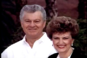 Lee Young posing with his wife, Connie, a caucasian middle aged woman with short brown hair.