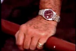A hand with a ring on the pinky and a gold watch holding a red railing.