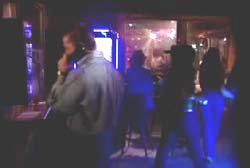 A bar, one man is on the payphone while women are walking up to the bar.