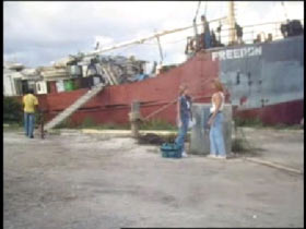 Three people standing on a dock infront of a freighter. The word 'Freedon' is painted on the bow of the ship.