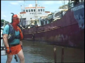 A man in a green and orange diving suit is standing on the dock up the Freedon freighter.