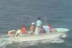 Five people wearing baseball caps in a small motor boat as it travels across the water.