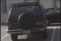 The back of a black Chevrolet SUV with a tire attached to the back.