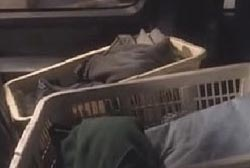 Two white baskets filled with folded laundry in the back seat of the SUV.